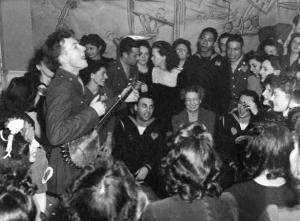 Peet Seeger singing in 1944 at the Washington Labor Canteen. Eleanor Roosevelt is seated in front between two service men.